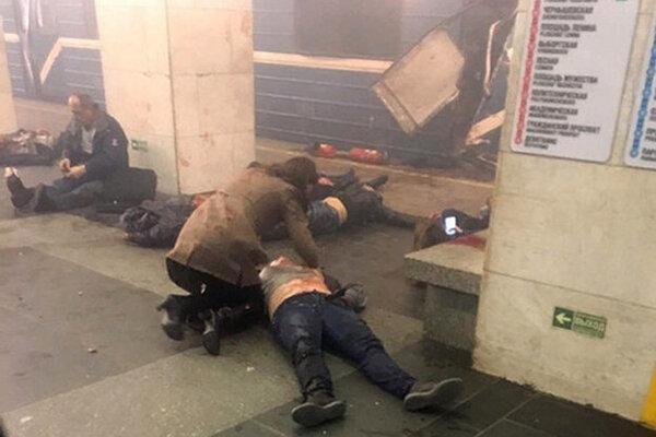 Obete výbuchu ležia na zemi pri zničenom vagóne metra na zastávke metra.