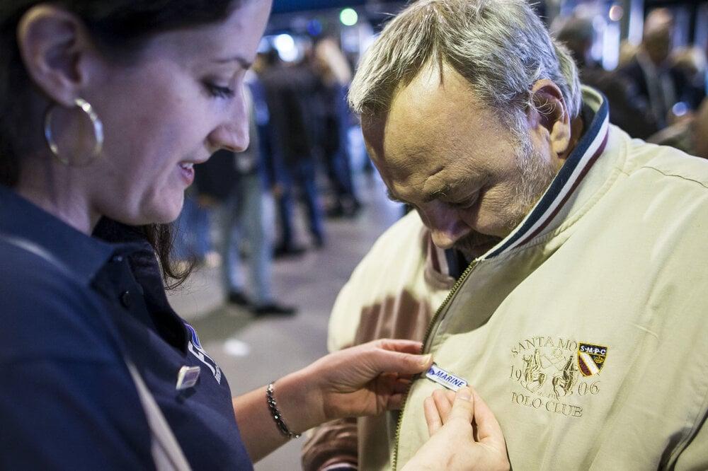 Dobrovoľníci predávajú pri vstupe suveníry s Le Penovej mottom.
