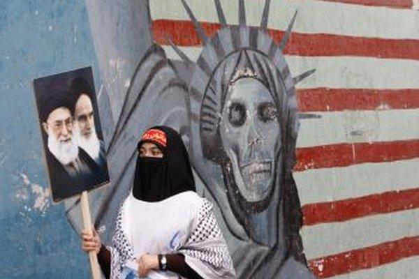 Moslimka nesie plagát s  portrétmi  ajatolláha Chomejního.