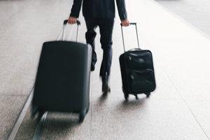 Muž s kufrom beží na letisku.