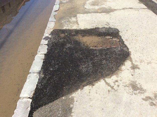 Kovovo-asfaltový poklop. Niekde na chodníku asfalt chýba, tu je zas navyše.