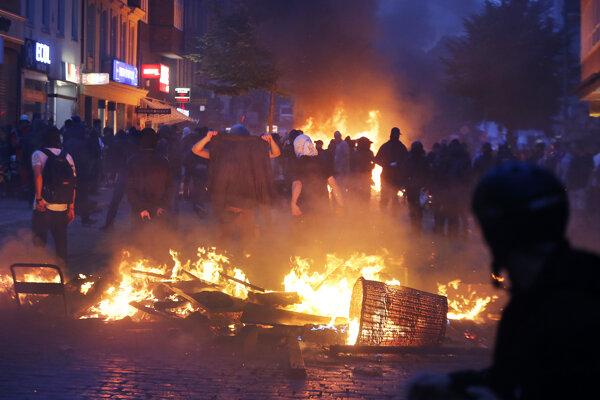 Demonštranti proti samitu krajín G20 stoja pred horiacou barikádou v nemeckom Hamburgu
