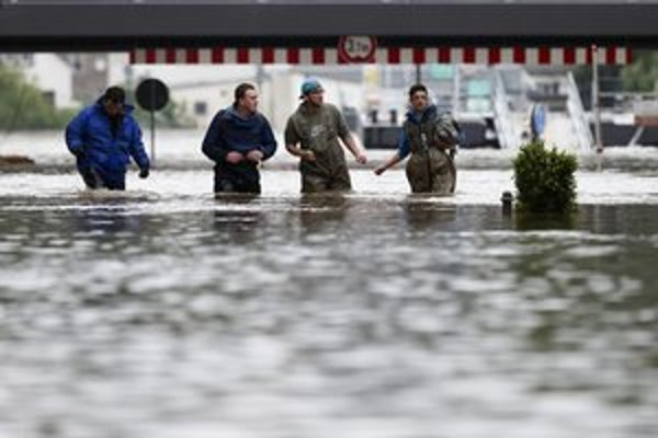 Dobrovoľníci kráčajú po zaplavenej ulici v nemeckom meste Pirna.