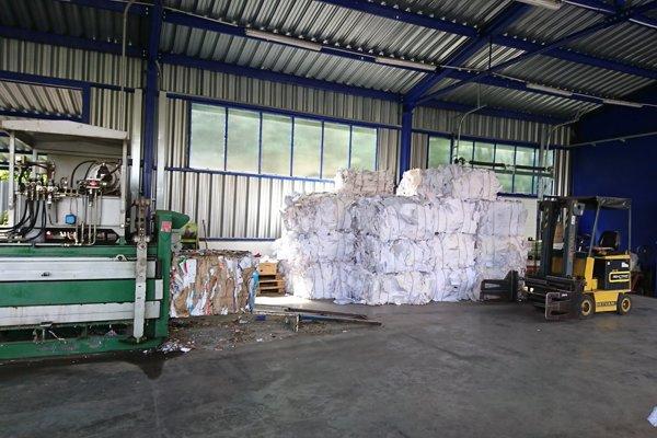 Pohľad do haly, v ktorej zberné suroviny lisujú papier.