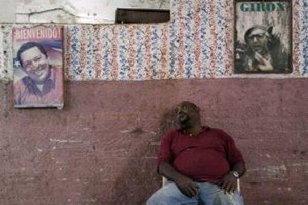 Predavač zeleniny odpočíva pod portrétmi venezuelského prezidenta Huga Cháveza.