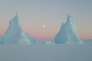 Dve veže. Pokojná a zamrznutá krajina antarktického morského ľadovca v zimných mesiacoch s Mesiacom.
