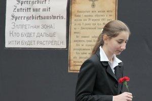 Dievča kráča vedľa nacistických oznamov počas odhalenia pamätníka obetiam masakry v rokline Babyn Jar.