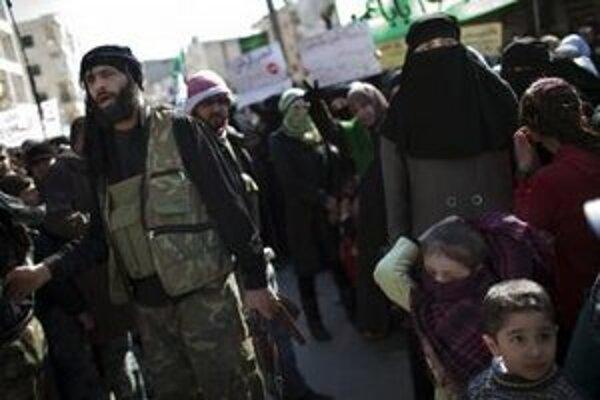 Vojak Slobodnej sýrskej armády stojí medzi demonštrantmi na protivládnom proteste v meste na severe Sýrie.