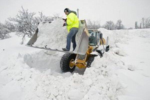 Buldozér odpratáva sneh z rumunskej obce Carnigul Mic.