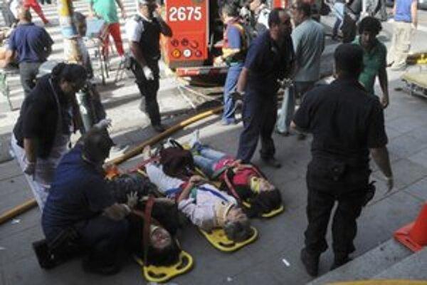 Zranení pasažieri čakajú na prevoz.