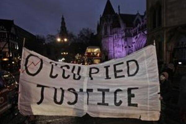 """Demonštranti z hnutia Occupy Londýn pochodujú s transparentom s heslom """"Okupovaná spravodlivosť""""."""