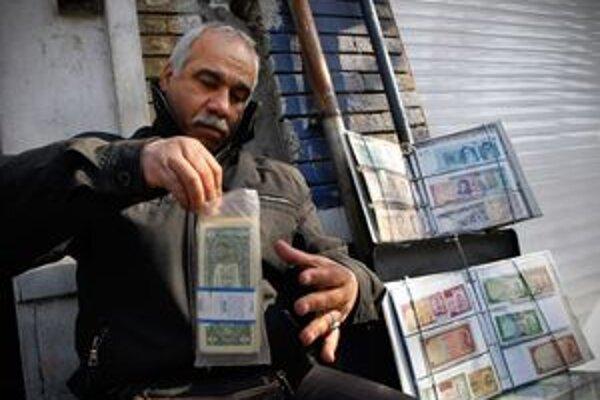 Pouličný díler ukladá do plastového vrecka americké doláre.