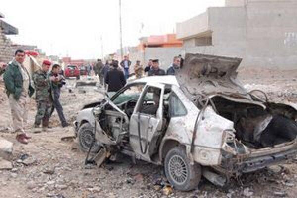 Príslušníci irackých bezpečnostných síl vyšetrujú výbuch nálože nastraženej v automobile.