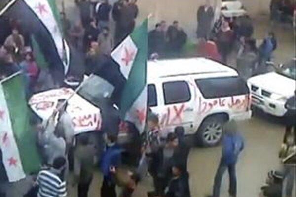 Vozidlo pozorovateľov Ligy arabských štátov uprostred davu.
