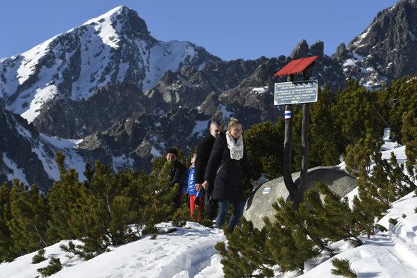 Turisti sa vracajú od informačnej tabule po prečítaní oznamu o uzávere chodníkov neďaleko Chaty pod Soliskom pri odbočke do Furkotskej doliny, vľavo v pozadí je štít Kriváň.