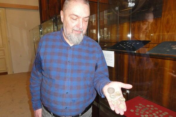 Numizmatik múzea Vladimír Bíroš ukazuje zaujímavé mince výstavy.