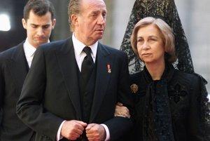 Španielsky kráľ Juan Carlos (uprostred) sa zhovára so svojou manželkou kráľovnou Sofiou (vpravo) 13. januára počas odchodu z kláštora El Escorial po zádušnej omši za kráľovú matku, Mariu de las Mercedes de Borbon y Orleans v januári 2000. Za nimi kráča ich syn, korunný princ Felipe (vľavo).