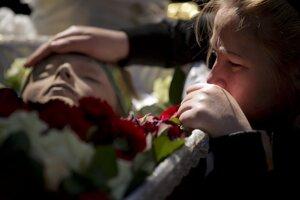 Príbuzná plače počas pohrebu sedemnásťročného chlapca, ktorý zahynul v piatok pri skoku z horiacej budovy domu odborov v Odese.