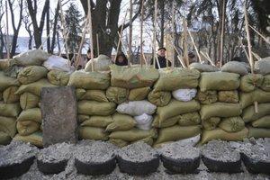 Protesty na Ukrajine aj naďalej pokračujúProtestujúci chránia barikádu.