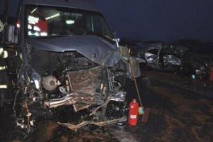 Zničená predná časť mikrobusu, vzadu vrak osobného auta..