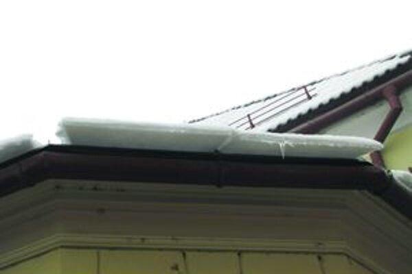Sneh na strechách budov dlho nevydržal. Zosunul sa.