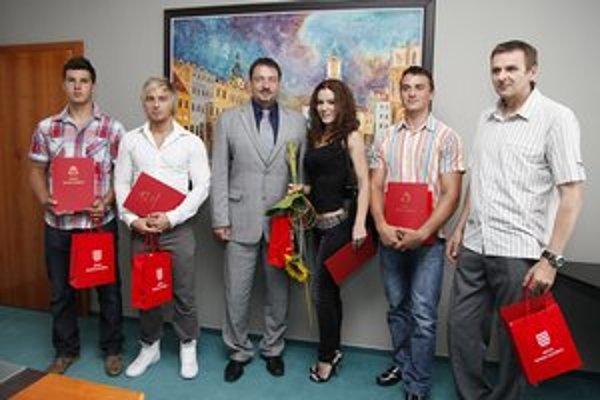 Spolu s trénerom  Petrom Búvalom (vpravo) si z  rúk primátora Petra Gogolu (v strede) prevzali ďakovné listy.