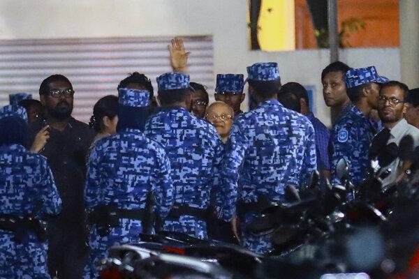 Exprezident Maledív a vodca opozície Maumún Abdal Gajúm obkľúčený príslušníkmi bezpečnostných síl.