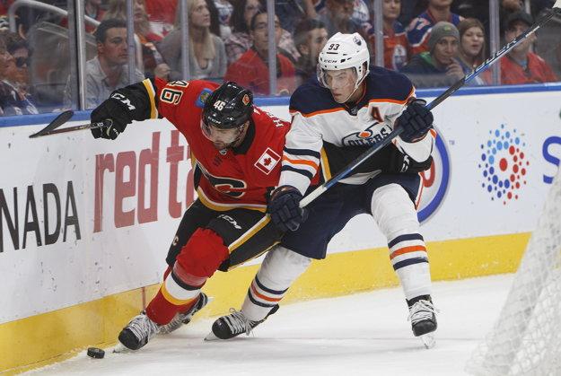 Za Calgary nastúpil Marek Hrivík (vľavo) zatiaľ v troch zápasoch. Na snímke bojuje o puk s Ryanom Nugentom-Hopkinom z Edmontonu.