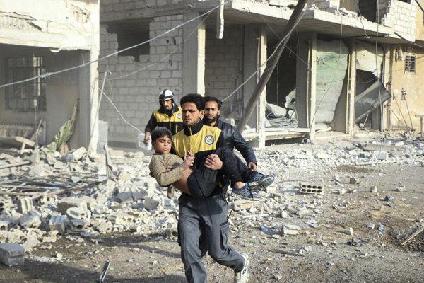 Dobrovoľníci odnášajú zraneného chlapca po útokoch sýrskych vládnych síl.