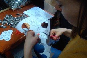 Dobrovoľníci vyrábajú odznaky na pochod.