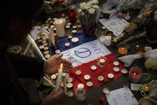Ľudia zapaľujú sviečky na Place de la République v Paríži.