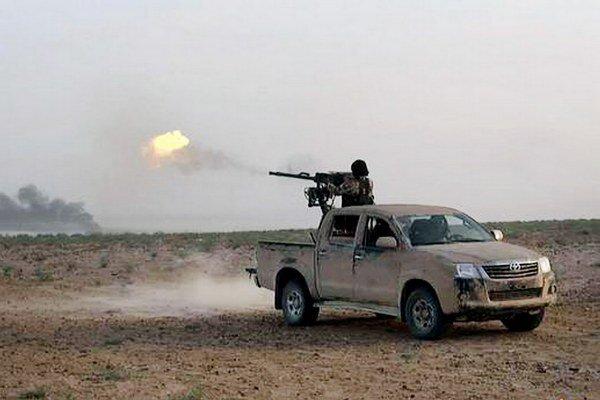 Militant Islamského štátu strieľa z ťažkej zbrane počas bojov so sýrskymi vládnymi silami na ceste medzi mestami Homs a Palmýra.