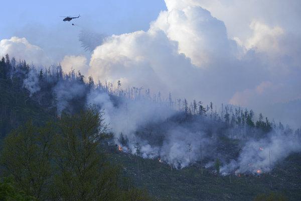 Pri hasení požiaru pomáhajú vrtuľníky.