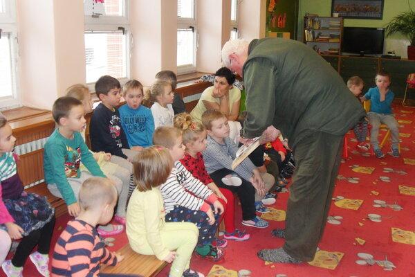 Poľovník fotky zvieratiek deťom ukazoval v knihe.
