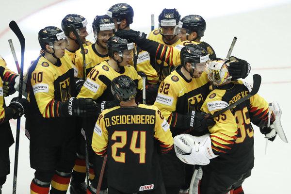 Hokejisti Nemecka oslavujú prekvapivý triumf nad Fínskom.