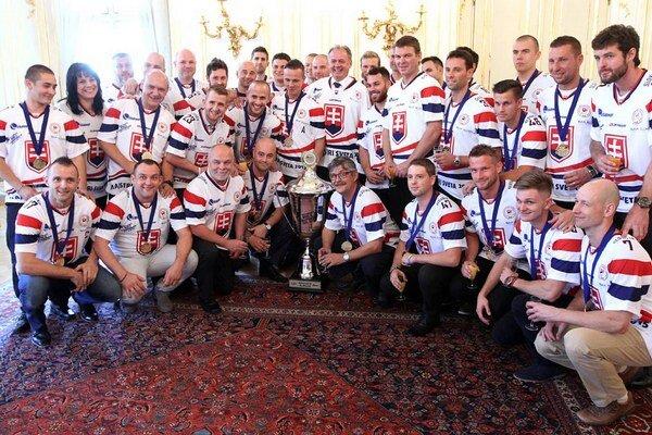 Hokejbalisti na fotke s prezidentom Andrejom Kiskom, medailami a víťazným pohárom.