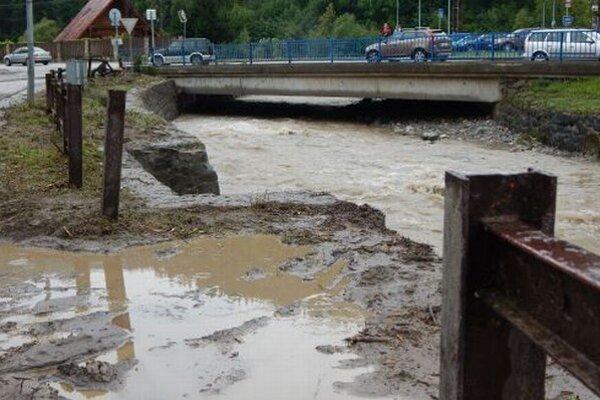 Rozvodnená rieka Varínka pretekajúca obcou, druhý deň po prietrži.