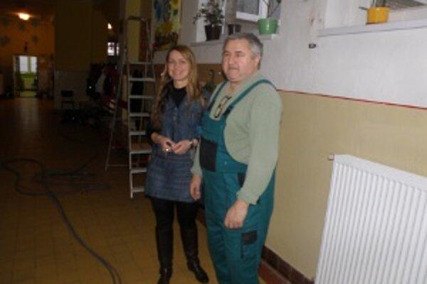 Riaditeľka školy Mária Torousová so školníkom V. Brezánim pri nových radiátoroch.