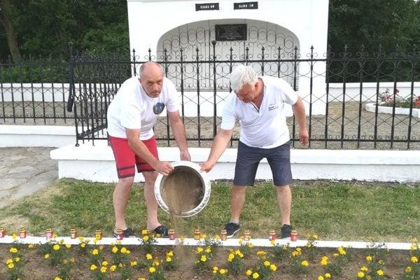 Jaroslav kráľ (vpravo) a Miroslav Cambál sypú hlinu zo Slovenska na hrob vojakov v Kragujevaci.