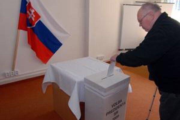 Dôchodca vhadzuje svoj hlasovací lístok do urny v Nemocnici s poliklinikou Žilina.