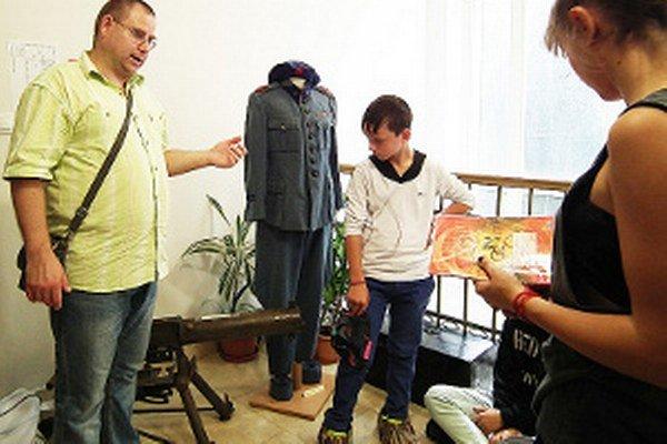 Historik Martin Chmelík ukazuje žiakom zo Základnej školy Petra Škrabáka zaujímavé exponáty.