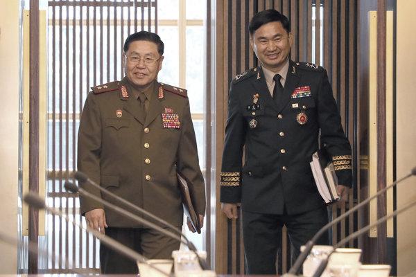 Severokórejský generálporučík An Ik-san (vľavo) a jeho juhokórejská náprotivok generálmajor Kim To-gjun si podávajú ruky počas stretnutia v pohraničnej dedine Pchanmundžom v tzv. Dome mieru, ktorý sa nachádza na juhokórejskej strane hranice.