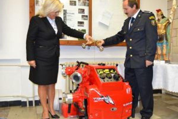 Starostka Viera Mazúrová krstí spolu s Rudolfom Brisudom, predsedom dobrovoľných hasičov, nové čerpadlo.
