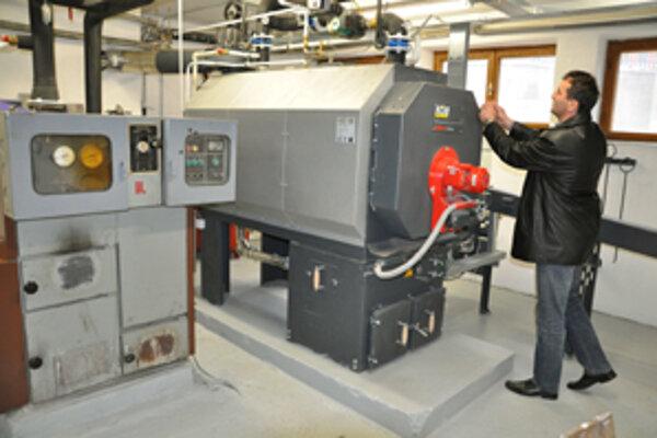 Starosta Metod Sojčák kontroluje plnoautomatický kotol na biomasu. Vedľa stojí starý kotol na uhlie.