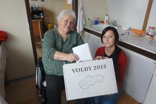 Podpredsedníčka volebnej komisie Silvia Michalková (vpravo) s prenosnou volebnou urnou.