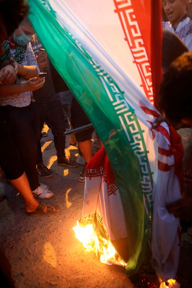 Protestujúci pália iránsku vlajku.