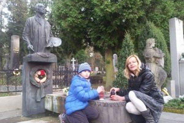 Učiteľka so žiakom zapaľujú sviečky na hrobe Martina Benku.