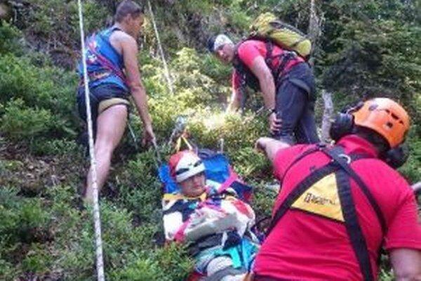 Zafixovanú ženu nesú záchranári po ferrate.