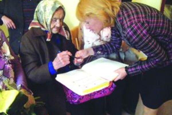 Storočnej babičke Márii Dvořákovej vystrojili dve oslavy. Druhú jej urobila obec. Na snímke pri podpise do kroniky s poslankyňou Gabrielou Matejčíkovou.