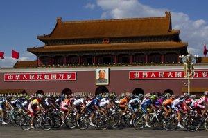 Cyklisti prechádzajú cez Námestie brány nebeského pokoja v Pekingu.